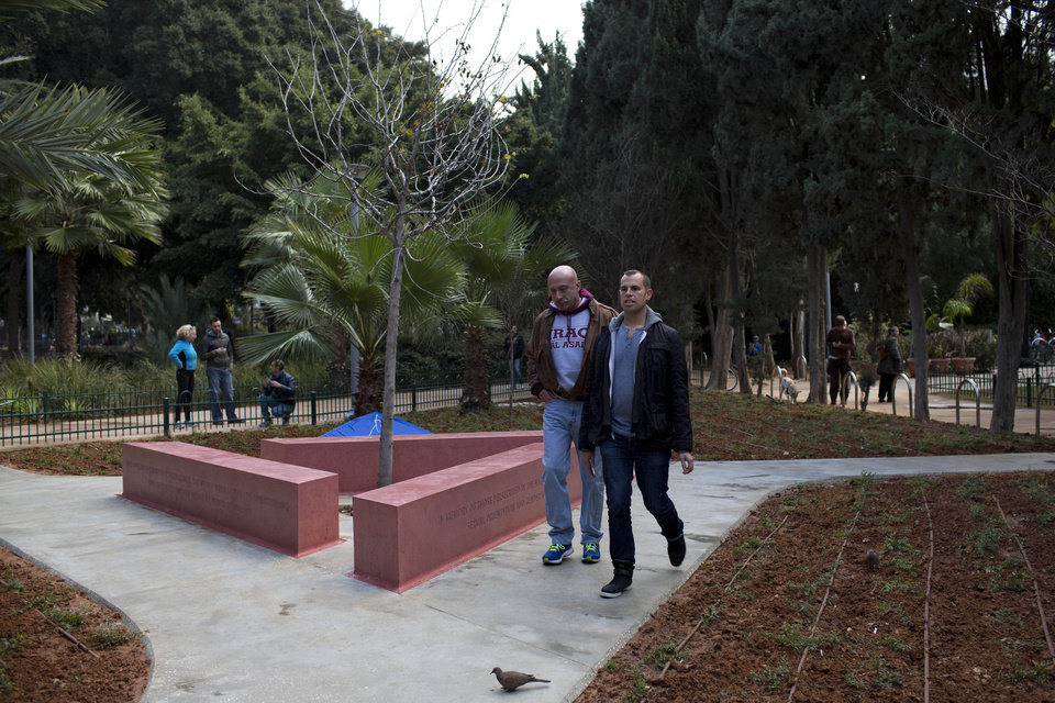 Photo - People walk by a new monument honoring gays and lesbians persecuted by the Nazis during World War II for their sexual orientation and gender identity, In Tel Aviv, Israel, Friday, Jan. 10, 2014. The landmark joins similar memorials in Berlin, Amsterdam, Sydney and San Francisco dedicated to gay victims of the Holocaust. While Israel has scores of monuments for the genocide, the Tel Aviv memorial is the first that deals universally with Jewish and non-Jewish victims alike. (AP Photo/Oded Balilty)