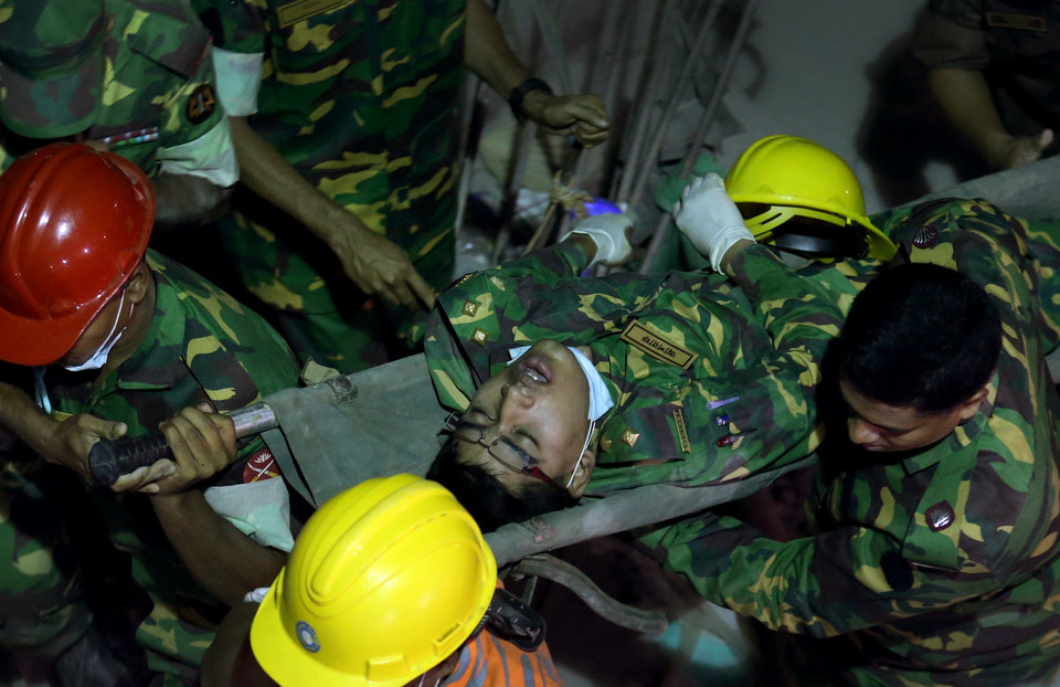 Photo - A soldier is evacuated from a fire which broke out in a garment factory building which collapsed Wednesday in Savar, near Dhaka, Bangladesh, Sunday April 28, 2013. A fire broke out late Sunday in the wreckage of the garment factory that collapsed last week in Bangladesh, with smoke pouring from the piles of shattered concrete and some of the rescue efforts forced to stop. The fire came four days after the collapse, as rescuers were trying to free a woman they found trapped in the rubble.(AP Photo/Wong Maye-E)