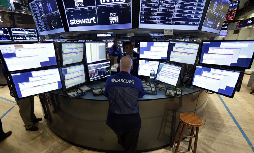 Photo - Specialist John O'Hara works Thursday at his post on the floor of the New York Stock Exchange. AP Photo  Richard Drew