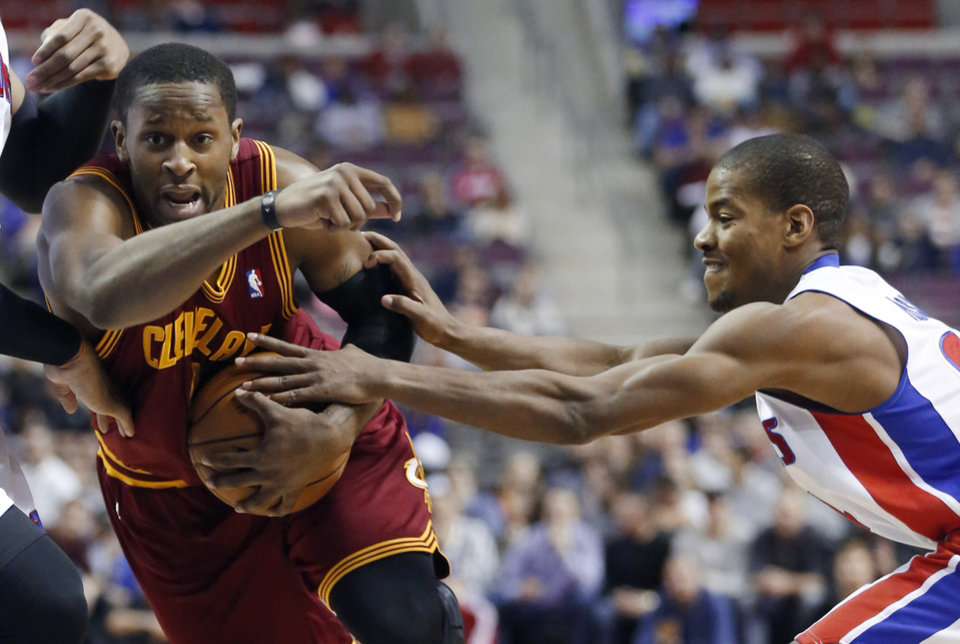 Photo - Cleveland Cavaliers guard C.J. Miles, left, is fouled by Detroit Pistons guard Kim English while driving to the basket in the first half of an NBA basketball game Friday, Feb. 1, 2013, in Auburn Hills, Mich. (AP Photo/Duane Burleson)