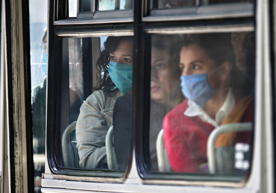 Photo - Some bus riders wore masks Tuesday in downtown Mexico City. AP PHOTO