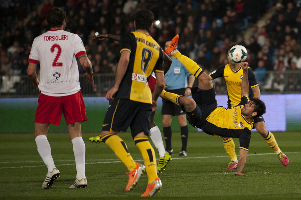 Photo - Atletico's Diego Costa from Brazil, right, in action with Marco Torsiglieri from Argentina, left, and Raul Garcia, center, during a Spanish La Liga soccer match between Almeria and Atletico de Madrid at the Juegos Mediterraneos stadium in Almeria, Spain Saturday Feb. 8, 2014. (AP Photo/Daniel Tejedor)