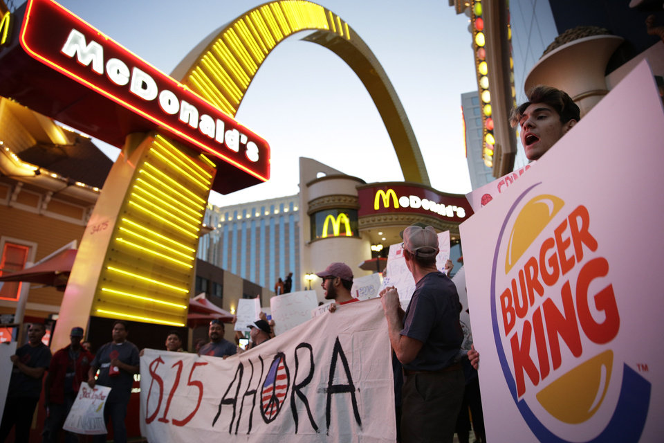 Photo - Protestors, including Kris Varrette, right, chant for increased wages and union rights at fast food restaurants Thursday, Sept. 4, 2014, in Las Vegas. Police detained several protesters in cities nationwide Thursday as they blocked traffic in the latest attempt to escalate their efforts to get McDonald's, Burger King and other fast-food companies to pay their employees at least $15 an hour. (AP Photo/John Locher)
