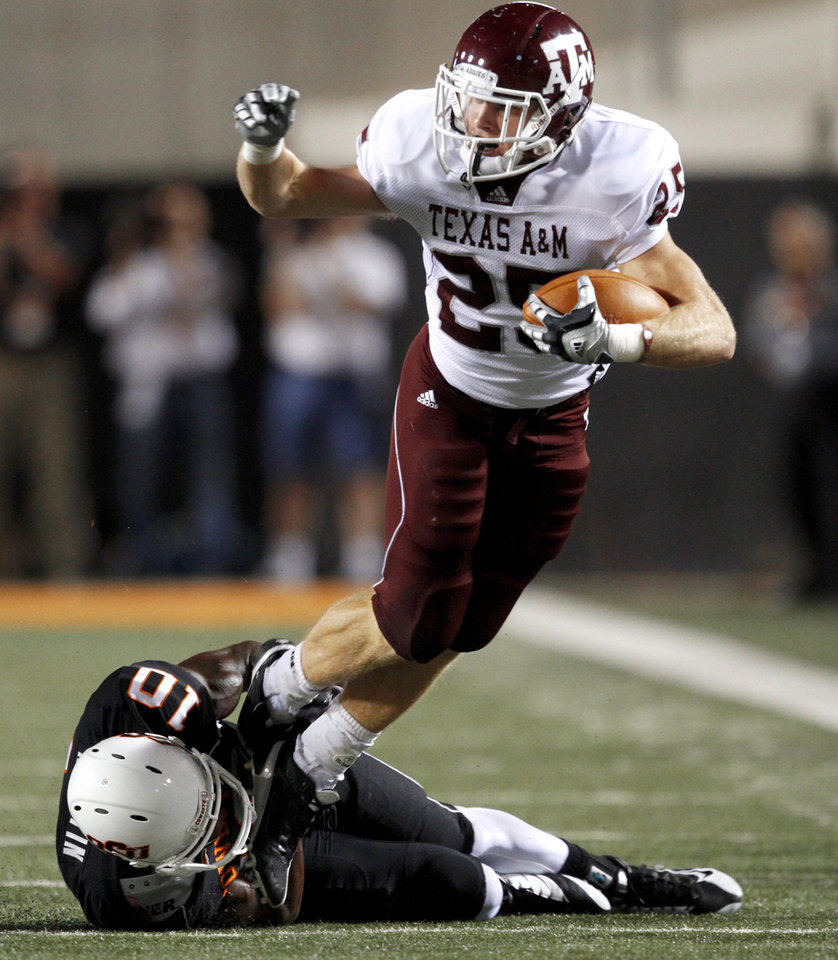 Photo - Texas A&M's Ryan Swope tries to get past OSU's Markelle Martin during the college football game between Texas A&M University and Oklahoma State University (OSU) at Boone Pickens Stadium in Stillwater, Okla., Thursday, Sept. 30, 2010. Photo by Bryan Terry, The Oklahoman