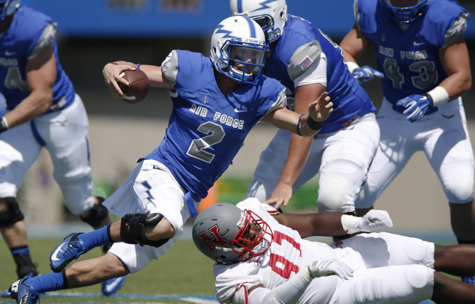 Photo - Air Force quarterback Kale Pearson, front, runs for a short gain past Nicholls State linebacker Jeremiah Thomas in the second quarter of an NCAA college football game at Air Force Academy, Colo., on Saturday, Aug. 30, 2014. (AP Photo/David Zalubowski)