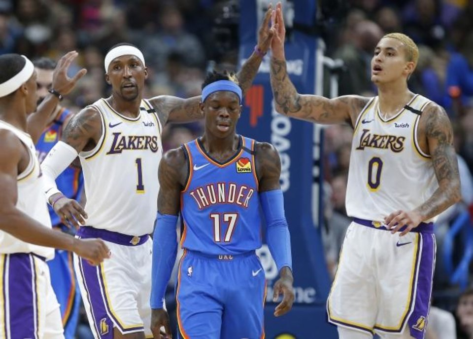 Photo -  Los Angeles' Kyle Kuzma (0) and Kentavious Caldwell-Pope (1) slap hands behind Oklahoma City's Dennis Schroder (17) during the Lakers' 125-110 win Saturday at Chesapeake Energy Arena. [Bryan Terry/The Oklahoman]