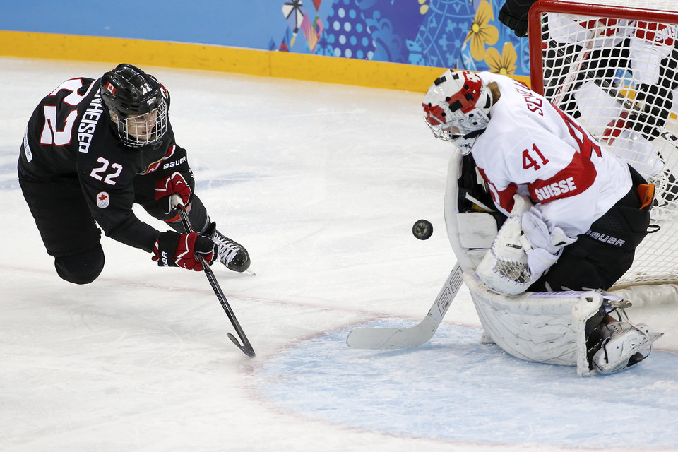Photo - Goalkeeper Florence Schelling of Switzerland blocks Hayley Wickenheiser of Canada shot on the goal during the third period of the women's ice hockey game at the Shayba Arena during the 2014 Winter Olympics, Saturday, Feb. 8, 2014, in Sochi, Russia. (AP Photo/Petr David Josek)