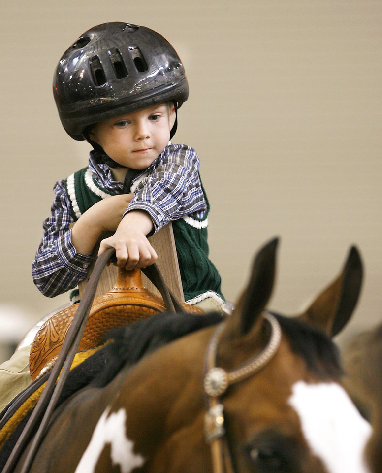 Jimmy, 4, of Shawnee rides Patch the horse at State Fair Park during a special exhibition at the Oklahoma Holiday Classic, a horse show organized by the Oklahoma Paint Horse Club. Jimmy and his two brothers were among nine riders who participated in horse therapy exhibition. Photo BY JIM BECKEL, THE OKLAHOMAN
