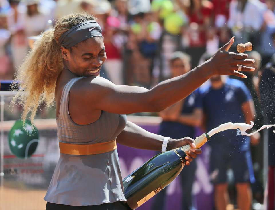 Photo - Serena Williams sprays sparkling wine as she celebrates after winning the final against Italy's Sara Errani at the Italian Open tennis tournament, in Rome, Sunday, May 18, 2014. Serena Williams kept the crowd from being a factor in a 6-3, 6-0 victory over 10th-seeded Sara Errani to win the Italian Open for the third time Sunday. (AP Photo/Gregorio Borgia)