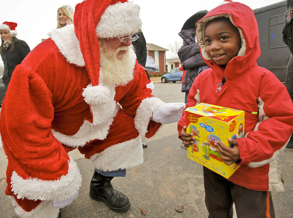 "CHILD / CHILDREN / KIDS: Kamauri Harris, 3, gets a gift from Santa Claus, who stopped by the Heritage Pointe Apartments to hand out gifts to kids that reside at the apartments in Oklahoma City, Okla. on Thursday, Dec. 22, 2011. Dr. Harvey Jenkins and Kyle Guffey, two Oklahoma City businessmen organized ""Toys in the Hood,"" a program through which local businesses offer discounts in exchange for toy donations.  Photo by Chris Landsberger, The Oklahoman"