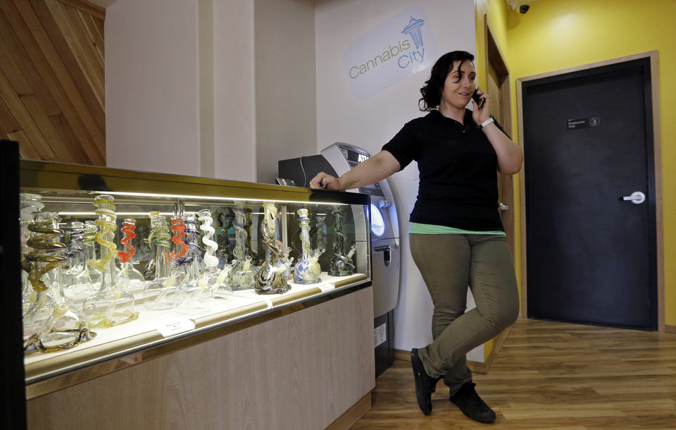 Photo - Cannabis City manager Amber McGowan takes the marijuana shop's first call, from a potential customer, days before the grand opening Wednesday, July 2, 2014, in Seattle. The store expects to begin selling pot Tuesday, July 8, the first day that recreational marijuana can legally be sold in Washington state and is expected to be the first licensed retailer in Seattle. (AP Photo/Elaine Thompson)