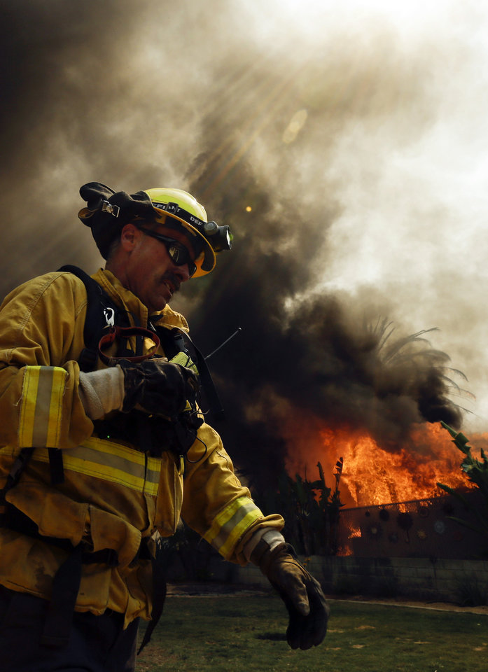 Photo - A firefighter moves past a burning structure during a wildfire Thursday, May 15, 2014, in Escondido, Calif. One of the nine fires burning in San Diego County suddenly flared Thursday afternoon and burned close to homes, trigging thousands of new evacuation orders. (AP Photo/Gregory Bull)