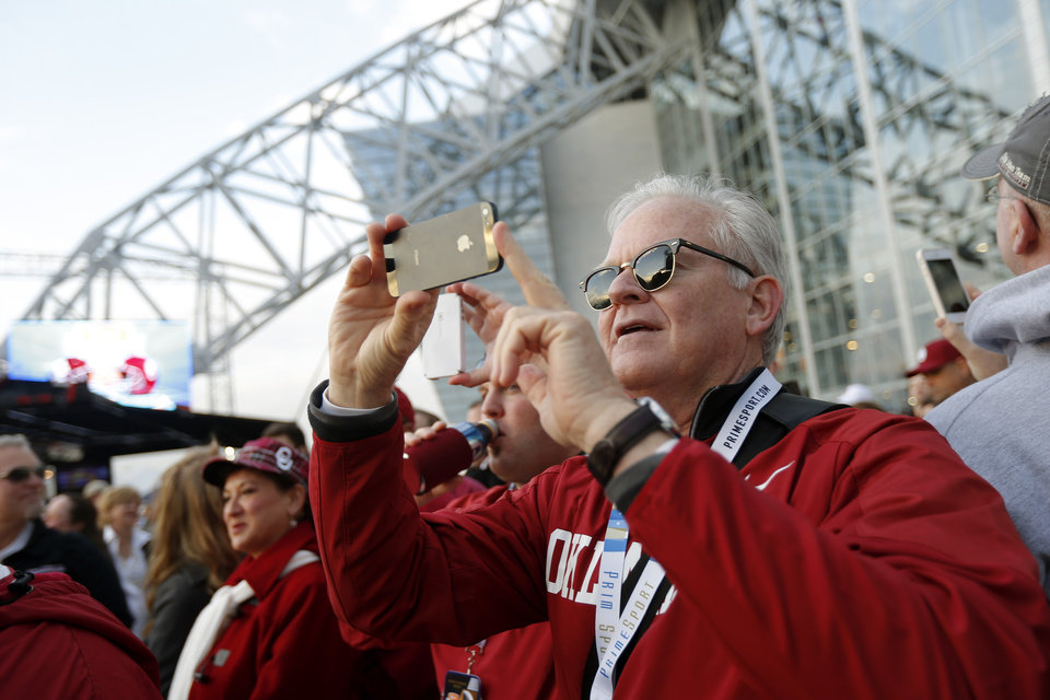 Photo - J.C. Skidmore of Crown Point, Indiana, takes a photo outside Cowboys stadium before the Cotton Bowl college football game between the University of Oklahoma (OU)and Texas A&M University at Cowboys Stadium in Arlington, Texas, Friday, Jan. 4, 2013. Photo by Bryan Terry, The Oklahoman