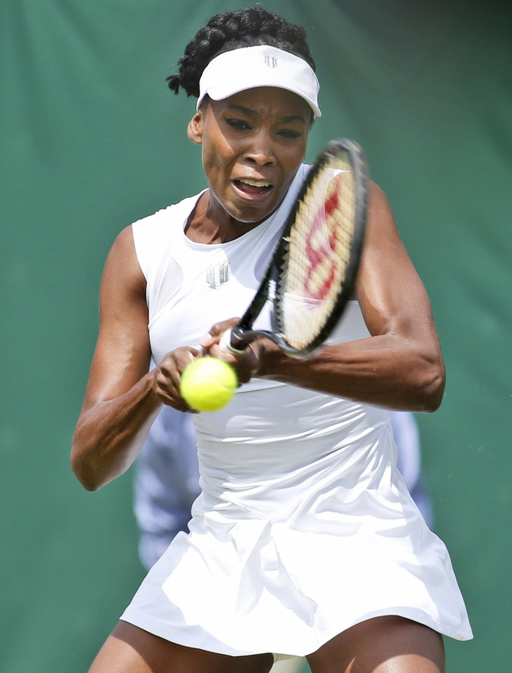 Photo - Venus Williams of U.S. returns to Kurumi Nara of Japan during their women's singles  match at the All England Lawn Tennis Championships in Wimbledon, London,  Wednesday, June 25, 2014. (AP Photo/Alastair Grant)