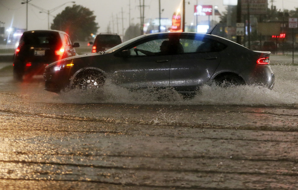 Photo - Cars drive through water at NW 39th and Meridian during heavy rain in Oklahoma City, Friday, May 31, 2013. Severe thunderstorms brought tornadoes, high winds, heavy rain and hail to central Oklahoma on Friday. Photo by Nate Billings, The Oklahoman
