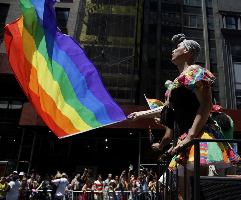 Photo - People on a float dance and wave flags during the Gay Pride Parade in New York, Sunday, June 29, 2014. Fifth Avenue became one big rainbow on Sunday, as thousands of participants waving multicolored flags made their way down the street for New York City's annual Gay Pride march. (AP Photo/Seth Wenig)