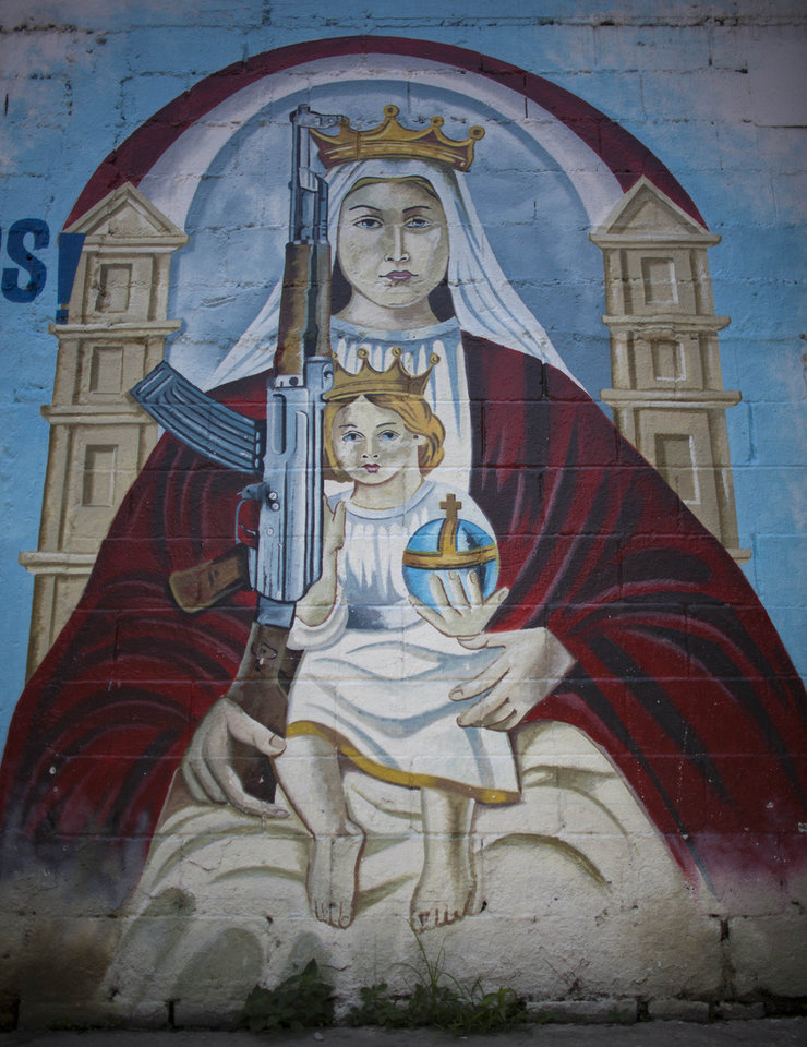 Photo -   In this Sept. 16, 2010, a mural depicts an image of the Virgen Mary holding Jesus and a machine gun in a wall in La Piedrita or Little Rock neighborhood gang turf in Caracas, Venezuela. Heavily armed gangs that pledge allegiance to President Hugo Chavez rule over fiefdoms in slums where police rarely patrol, employing vigilante justice and collecting extortion money. A shooting attack on the opposition candidate's entourage has kindled worries that Chavez's defenders could resort to violence if cancer impedes his bid for re-election. The gangs, however, are loosely organized and do not appear to be taking orders from the government. (AP Photo/Ariana Cubillos)