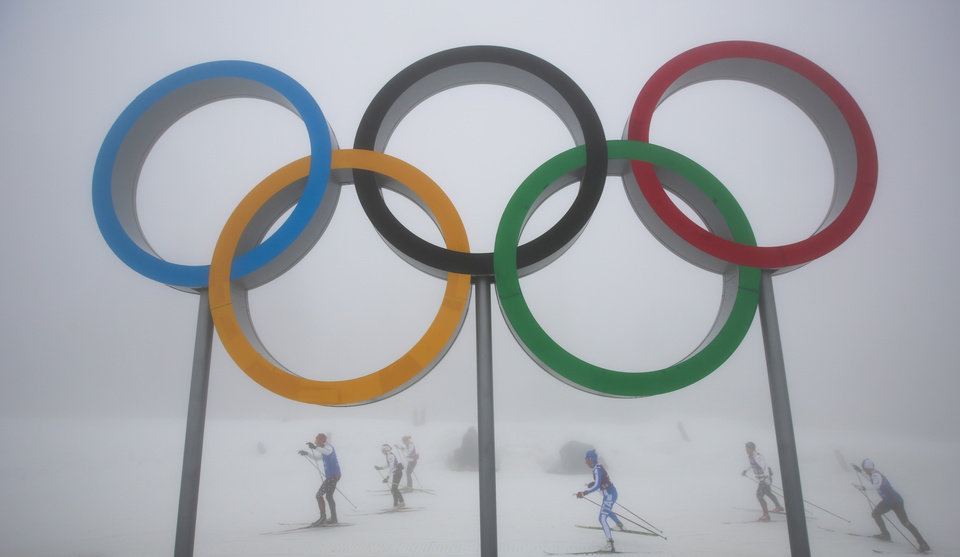 Photo - Cross-country skiers train underneath the olympic rings at the Laura biathlon and cross-country ski center, at the 2014 Winter Olympics, Monday, Feb. 17, 2014, in Krasnaya Polyana, Russia. After days of warm weather at the Sochi Olympics, fog up in the mountains is causing an even bigger disturbance. Thick fog rolled in over the mountains in Krasnaya Polyana on Sunday night and was still lingering on Monday, and the limited visibility forced organizers to delay a biathlon race and cancel the seeding runs in a snowboard event. (AP Photo/Gero Breloer)