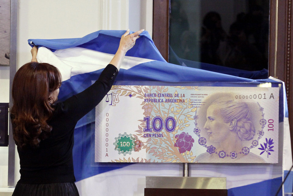 FILE - In this July 25, 2012 photo, Argentina\'s President Cristina Fernandez unveils an archetype of the new 100 Argentine pesos bill bearing the profile of former late first lady Maria Eva Duarte de Peron, better known as