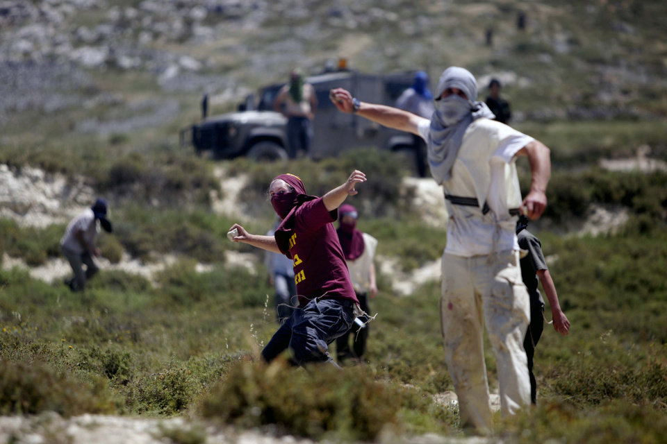 Photo - Jewish settlers throws rocks towards Palestinians, not pictured, during clashes near the Jewish settlement of Yitzhar, near Nablus, Tuesday, April 30, 2013. In the West Bank, a Palestinian man fatally stabbed an Israeli waiting at a bus stop and fired on police before he was detained by Israeli security forces, officials said. The Israeli military said that following the stabbing settlers began rioting, hurling rocks at Palestinian vehicles and setting fire to nearby fields. It said two rioters were arrested. (AP Photo/Nasser Ishtayeh)