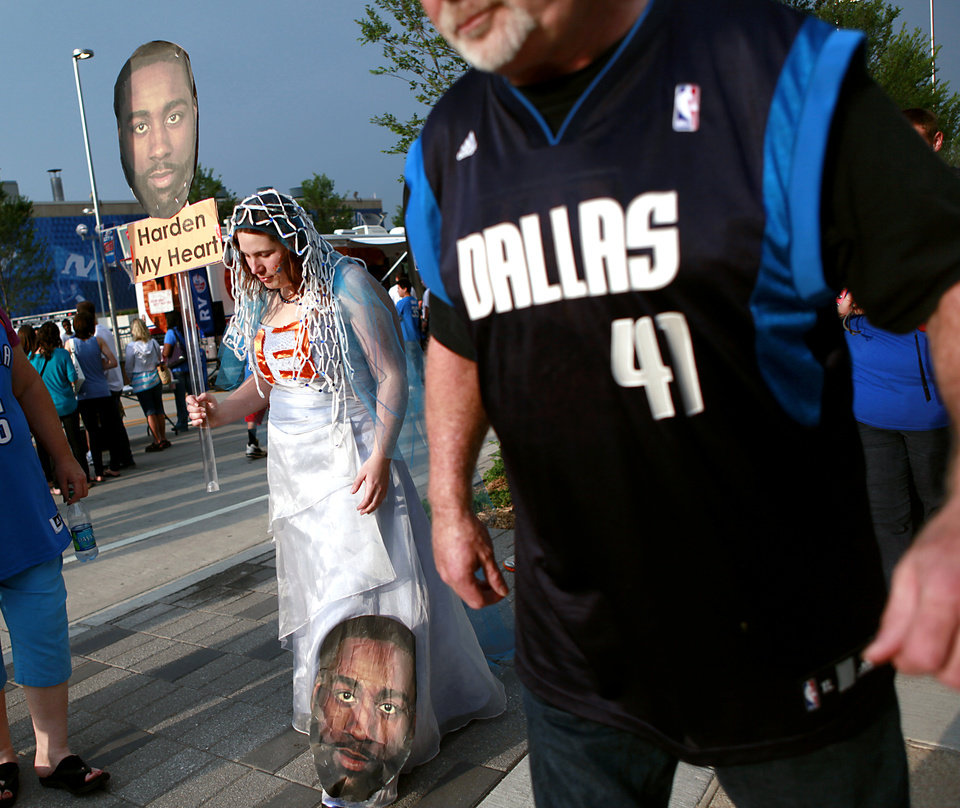 Photo - A Dallas Mavericks fan walks past Thunder fan Meghan Dailey (left) as she makes her way to the OKC Arena before game 4 of the Western Conference Finals in the NBA basketball playoffs between the Dallas Mavericks and the Oklahoma City Thunder at the Oklahoma City Arena in downtown Oklahoma City, Monday, May 23, 2011. Photo by John Clanton, The Oklahoman