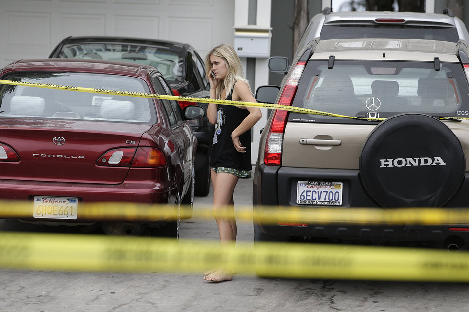 Photo - A college student talks on the phone near the scene of a shooting on Saturday, May 24, 2014, in Isla Vista, Calif. A drive-by shooter went on a rampage near a Santa Barbara university campus that left seven people dead, including the attacker, and others wounded, authorities said Saturday. (AP Photo/Jae C. Hong)