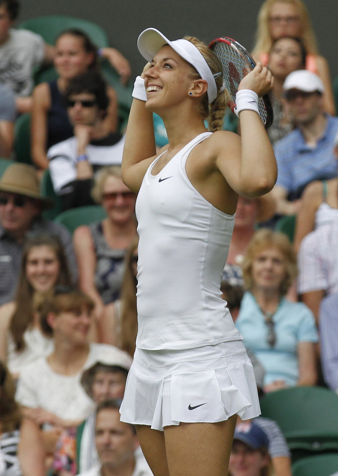 Photo - Sabine Lisicki of Germany smiles during her first round match against Julia Glushko of Israel at the All England Lawn Tennis Championships in Wimbledon, London, Tuesday, June 24, 2014. (AP Photo/Sang Tan)