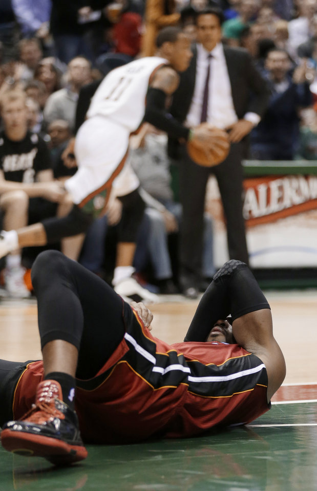 Photo - Miami Heat's Dwyane Wade reacts after hitting the floor during the first half of an NBA basketball game against the Milwaukee Bucks on Friday, March, 15 2013, in Milwaukee. (AP Photo/Jeffrey Phelps)