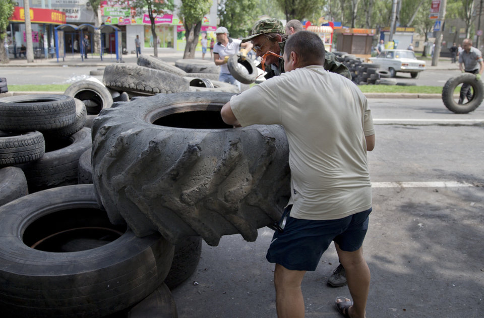 Photo - Pro-Russian men reinforce a barricade on the road to the airport in Donetsk, Ukraine, Wednesday, May 28, 2014. Scores of rebel fighters have been killed this week around the major eastern city of Donetsk, and Ukrainian border guards have reported at least one gun battle as they blocked groups of armed men trying to cross into Ukraine from Russia. Ukraine and the West have accused Moscow of fomenting the unrest, but Russian President Vladimir Putin has denied sending any troops to help the insurgents. (AP Photo/Vadim Ghirda)
