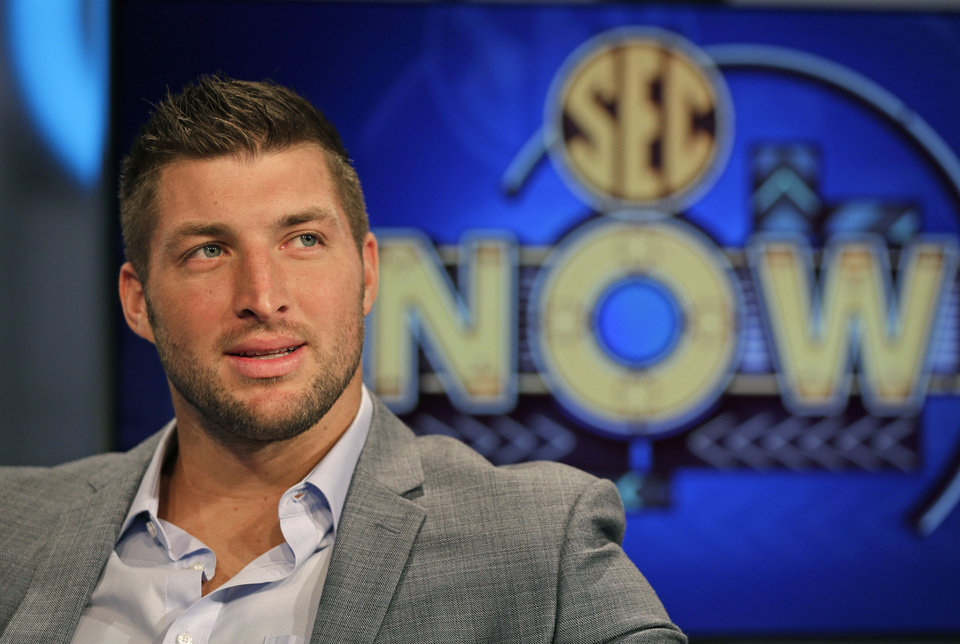 Photo - Tim Tebow ponders a question during an interview on the set of ESPN's new SEC Network in Charlotte, N.C., Wednesday, Aug. 6, 2014. Tebow has a new job as a commentator for the SEC Network, but is still looking for work in the NFL as a quarterback. (AP Photo/Chuck Burton)