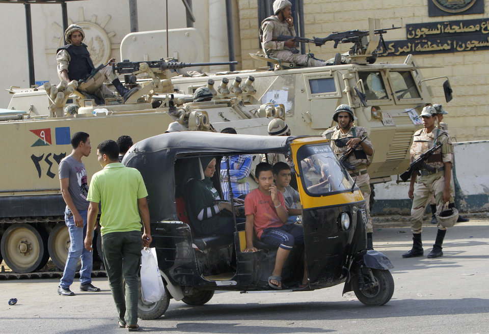 Photo - Egyptians drive their traditional tok-tok in front of armored vehicles guarding Torah Prison, where ousted President Hosni Mubarak is held in Cairo, Egypt, Wednesday, Aug. 21, 2013. An Egyptian court ordered Wednesday the release of ousted President Hosni Mubarak, but it is not yet clear if the ailing ex-leader will walk free after over two years in detention, officials said. The prospects of Mubarak's release after the 2011 uprising against him, and a slew of court cases that made him the first Arab leader to be tried by his own people, are likely to further fuel the rest that has hit Egypt following the military coup against his successor, the first freely elected president Islamist Mohammed Morsi. (AP Photo/Amr Nabil)