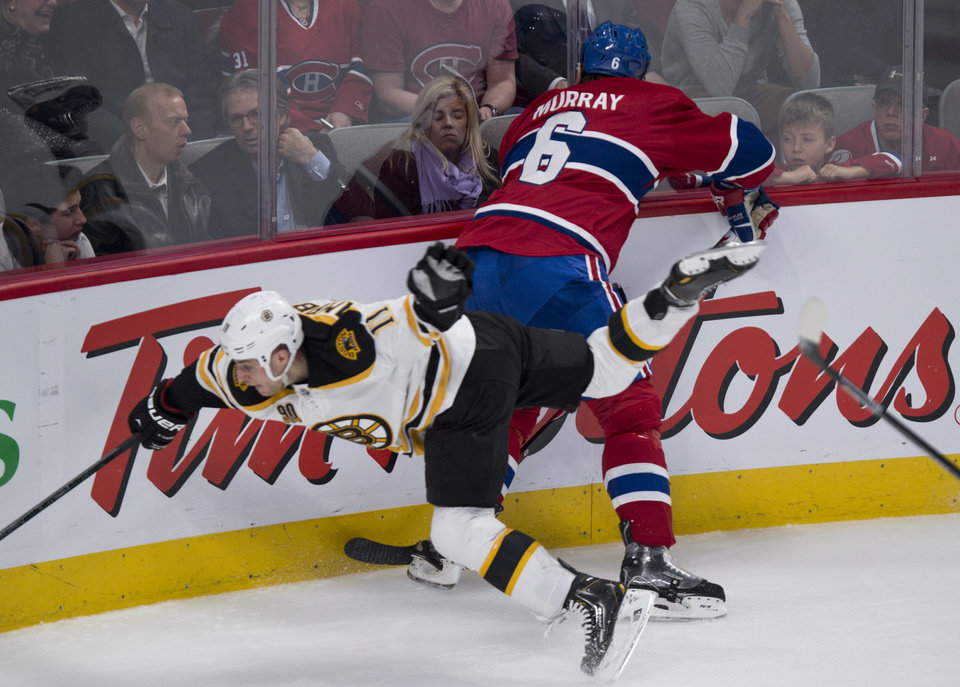 Photo - Boston Bruins' Gregory Campbell falls after hitting Montreal Canadiens' Douglas Murray during second period NHL hockey action Thursday, Dec. 5, 2013, in Montreal. (AP Photo/The Canadian Press, Paul Chiasson)