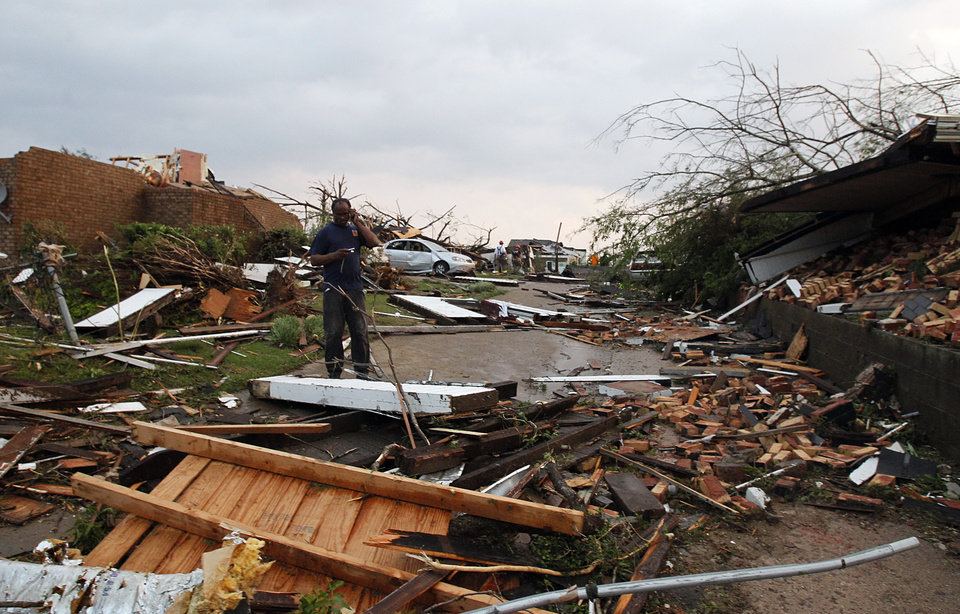 Photo - A homeowner surveys the damage to his neighborhood after a tornado hits Pratt City just north of downtown Birmingham on Wednesday, April 27, 2011, in Birmingham, Ala. (AP Photo/Butch Dill)
