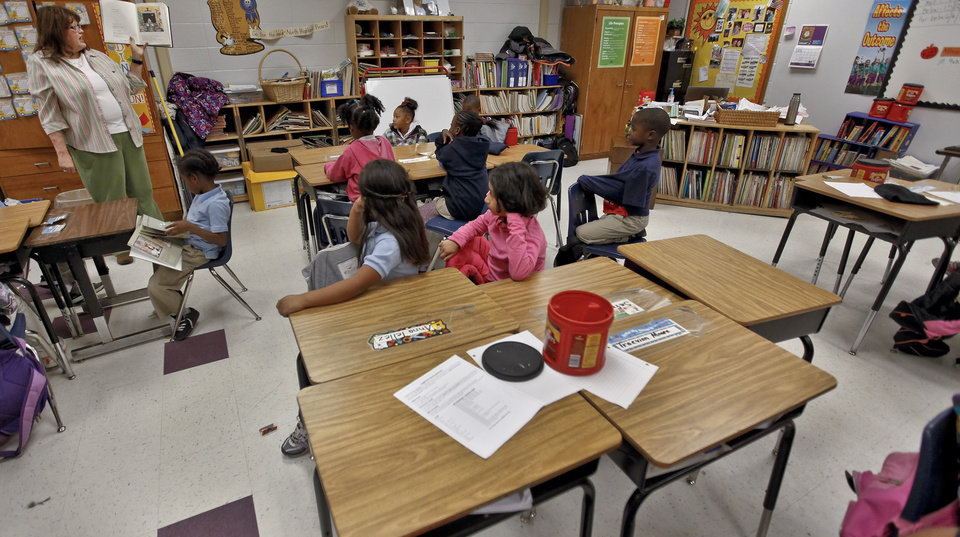 Photo - Desks sit empty in the first grade class of Michelle Kenery as students listen to her read a story at North Highland Elementary on Tuesday, Jan. 15, 2013, in Oklahoma City, Okla. The school has been one of the most effected in the metro by the arrival of flu season.   Photo by Chris Landsberger, The Oklahoman