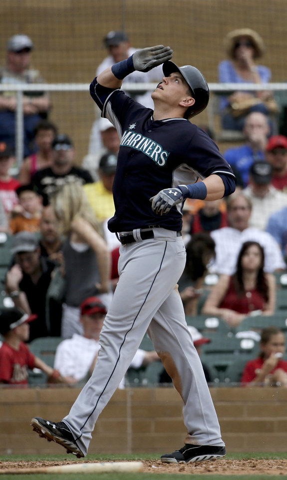 Photo - Seattle Mariners' Logan Morrison celebrates a solo home run against the Arizona Diamondbacks during the fifth inning of a spring exhibition baseball game in Scottsdale, Ariz., Thursday, March 13, 2014. (AP Photo/Chris Carlson)