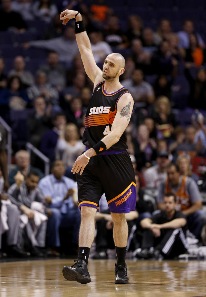 Phoenix Suns' Marcin Gortat, of Poland, reacts after making a shot against the San Antonio Spurs during the first half of an NBA basketball game, Sunday, Feb. 24, 2013, in Phoenix. (AP Photo/Matt York)