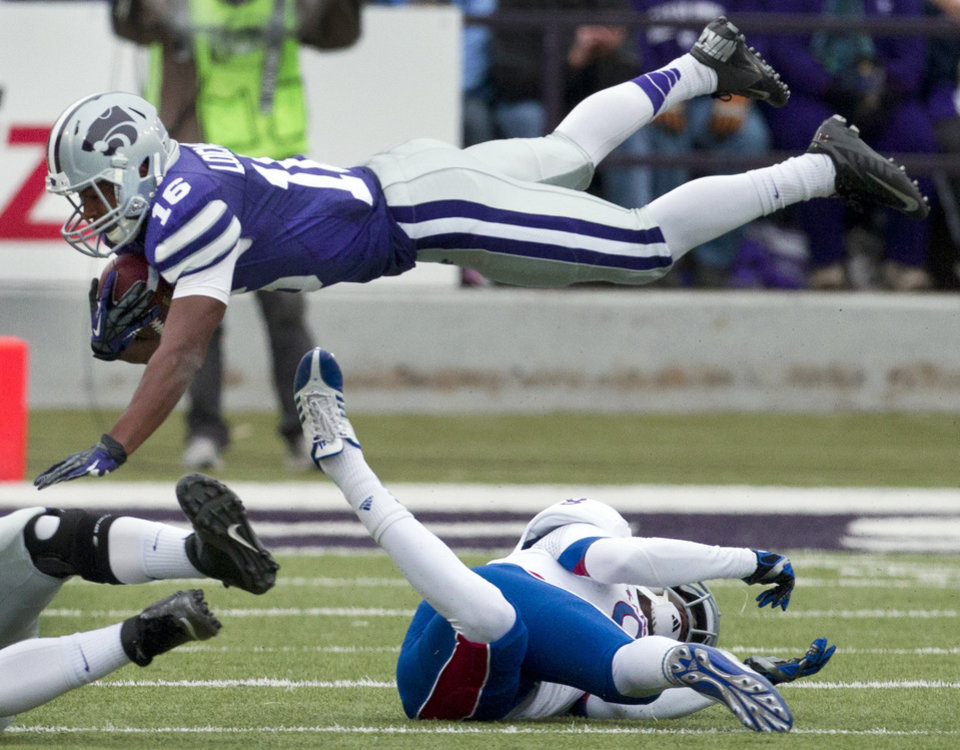 Kansas State\'s Tyler Lockett (16) is knocked into the air by Kansas\' Josh Ford (8) while returning a kick during the first half of an NCAA college football game in Manhattan, Kan., Saturday, Oct. 6, 2012. (AP Photo/Orlin Wagner) ORG XMIT: KSOW104