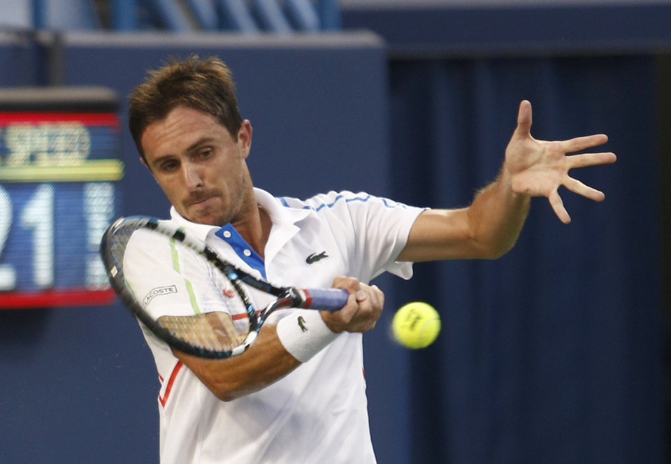 Photo - Edouard Roger-Vasselin, from France, returns a volley from Fabio Fognini, from Italy, in a first round match at the Western & Southern Open tennis tournament, Monday, Aug. 11, 2014, in Mason, Ohio. (AP Photo/David Kohl)