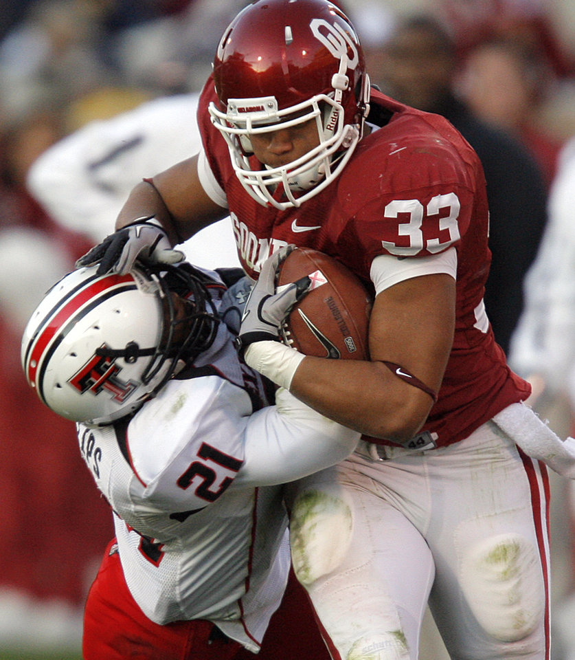 Photo - Oklahoma's Trey Millard (33) runs through Texas Tech's Jarvis Phillips (21)during the second half of the college football game between the University of Oklahoma Sooners (OU) and the Texas Tech Red Raiders (TTU) at the Gaylord Family Memorial Stadium on Saturday, Nov. 13, 2010, in Norman, Okla.  Photo by Chris Landsberger, The Oklahoman