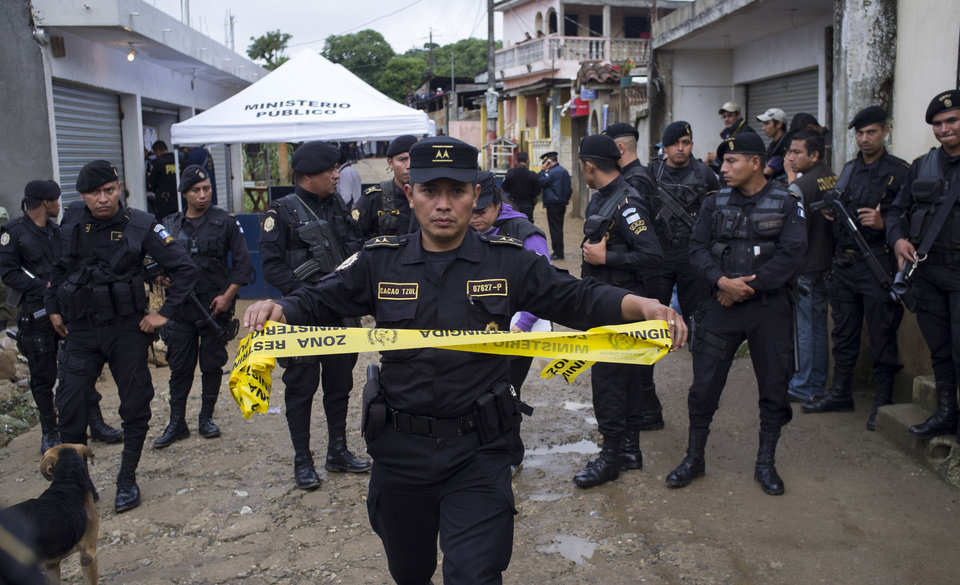 Photo - A Police agent prepares to set a police line after an attack in San Jose Zacahuil, on the outskirts of Guatemala City, Sunday, Sept. 8, 2013. Men firing from cars poured gunshots into three cantinas in a rural town in Guatemala, killing at least 10 people and injuring 19, local firefighters said Sunday. (AP Photo/Moises Castillo)