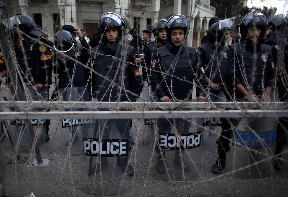 Egyptian riot police stand guard behind barbed wire while protesters chant anti Muslim Brotherhood slogans, not pictured, during a demonstration in front of the presidential palace, in Cairo, Egypt, Tuesday, Dec. 4, 2012. Thousands of Egyptians massed in Cairo Tuesday for a march to the presidential palace to protest the assumption by the nation\'s Islamist president of nearly unrestricted powers and a draft constitution hurriedly adopted by his allies. (AP Photo/Nasser Nasser)