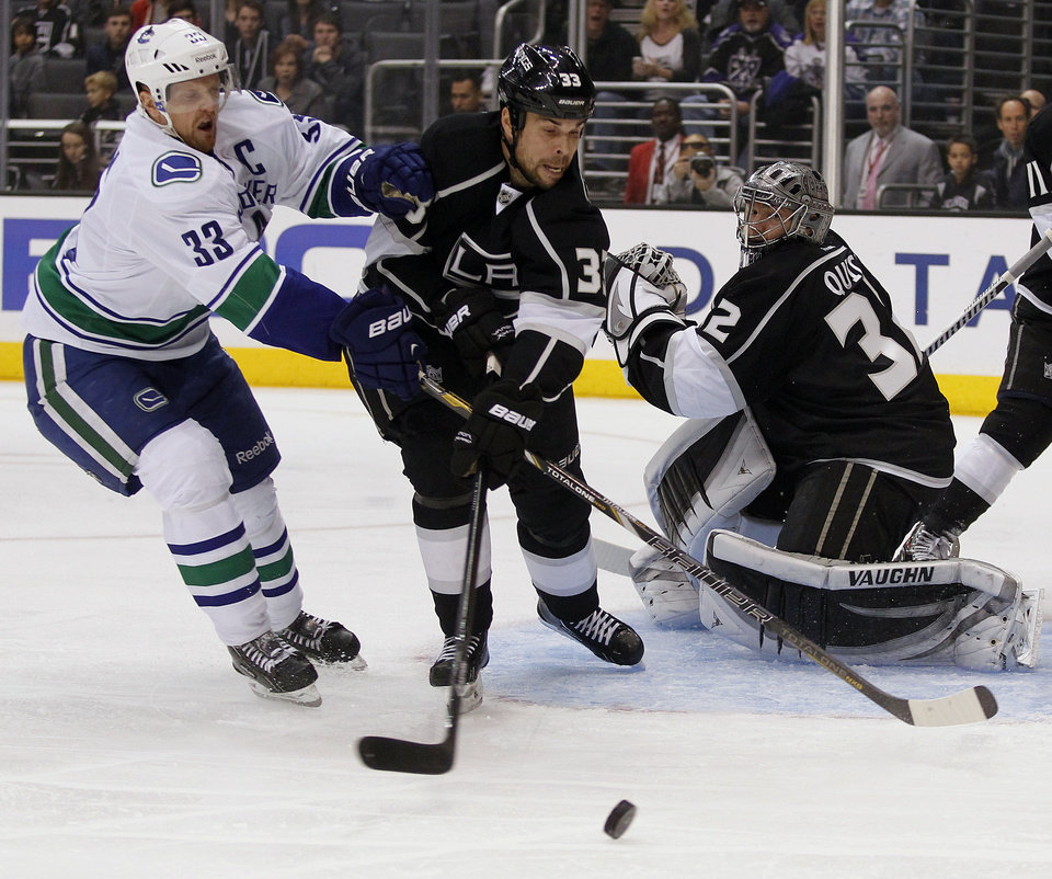 Photo - Vancouver Canucks center Henrik Sedin (33), of Sweden, and Los Angeles Kings defenseman Willie Mitchell (33) battle for the puck in front of goalie Jonathan Quick, right, during the first period of an NHL hockey game on Saturday, Jan. 4, 2014, in Los Angeles. (AP Photo/Alex Gallardo)