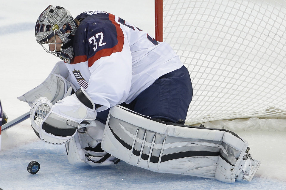 Photo - USA goaltender Jonathan Quick dives on the puck during the second period of the game against Slovakia during the 2014 Winter Olympics men's ice hockey tournament at Shayba Arena, Thursday, Feb. 13, 2014, in Sochi, Russia. (AP Photo/Matt Slocum)