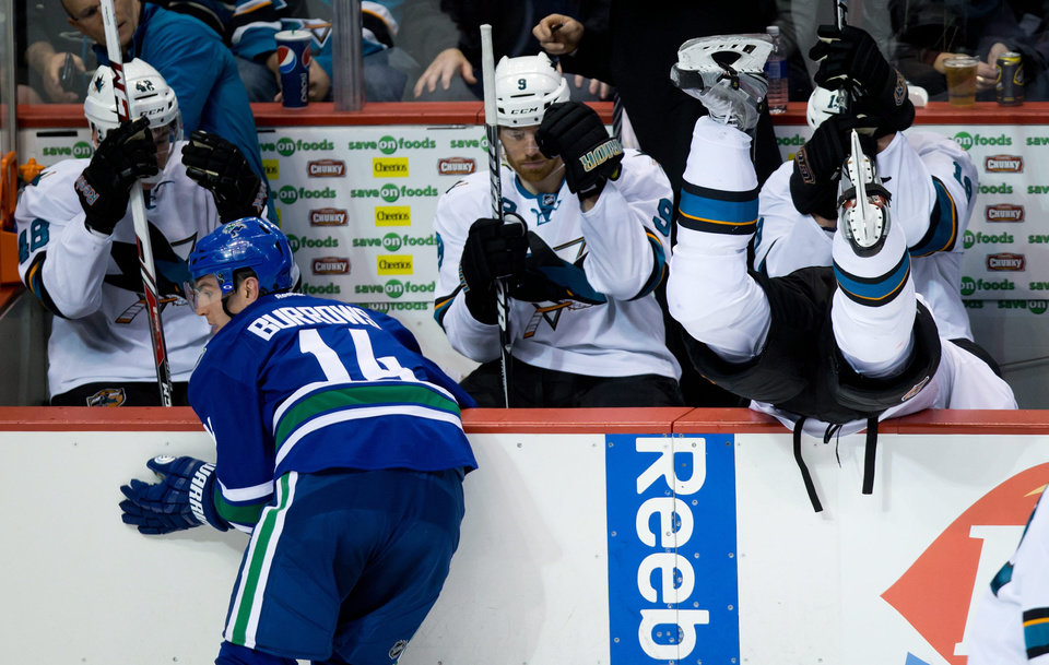 San Jose Sharks' Logan Couture, right, is checked into his team's bench by Vancouver Canucks' Alex Burrows, left, as Sharks' Tomas Hertl, of the Czech Republic, from left to right, Martin Havlat, of the Czech Republic, and Joe Thornton sit on the bench during second period NHL hockey action in Vancouver, British Columbia, on Thursday Nov. 14, 2013. (AP Photo/The Canadian Press, Darryl Dyck)