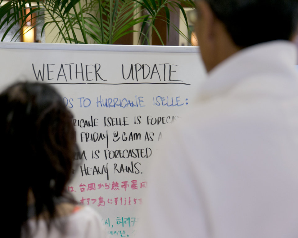 Photo - A couple reads a weather update written on a white board in the lobby of a hotel in Waikiki in Honolulu on Thursday, Aug. 7, 2014. With Iselle, Hawaii is expected to take its first direct hurricane hit in 22 years. Tracking close behind it is Hurricane Julio. (AP Photo/Marco Garcia)