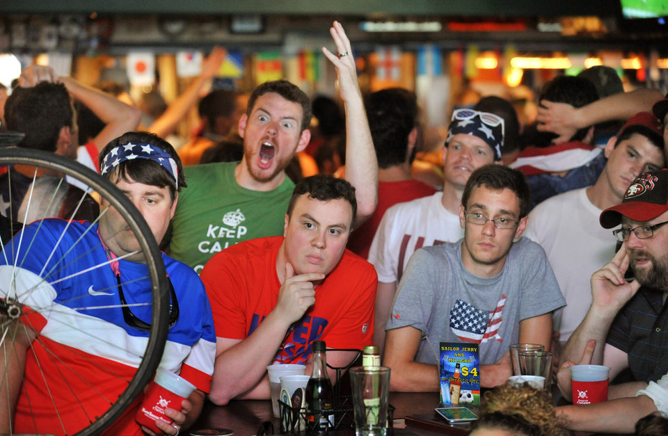 Photo - U.S. fans watch coverage of the closing minutes of a World Cup soccer match between the United States and Germany in Brazil, Thursday, June 26, 2014, at a pub in Jacksonville Beach, Fla. Germany won 1-0, but both teams advanced to the knockout round of the tournament. (AP Photo/The Florida Times-Union, Will Dickey)