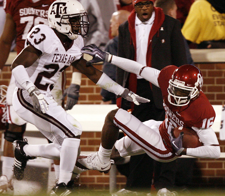 Photo - Oklahoma's Jaz Reynolds (16) pulls in a pass past Texas A&M's Steven Terrell (23) during the second half of the college football game between the University of Oklahoma Sooners (OU) and the Texas A&M Aggies at Gaylord Family-Memorial Stadium on Saturday, Nov. 14, 2009, in Norman, Okla. 