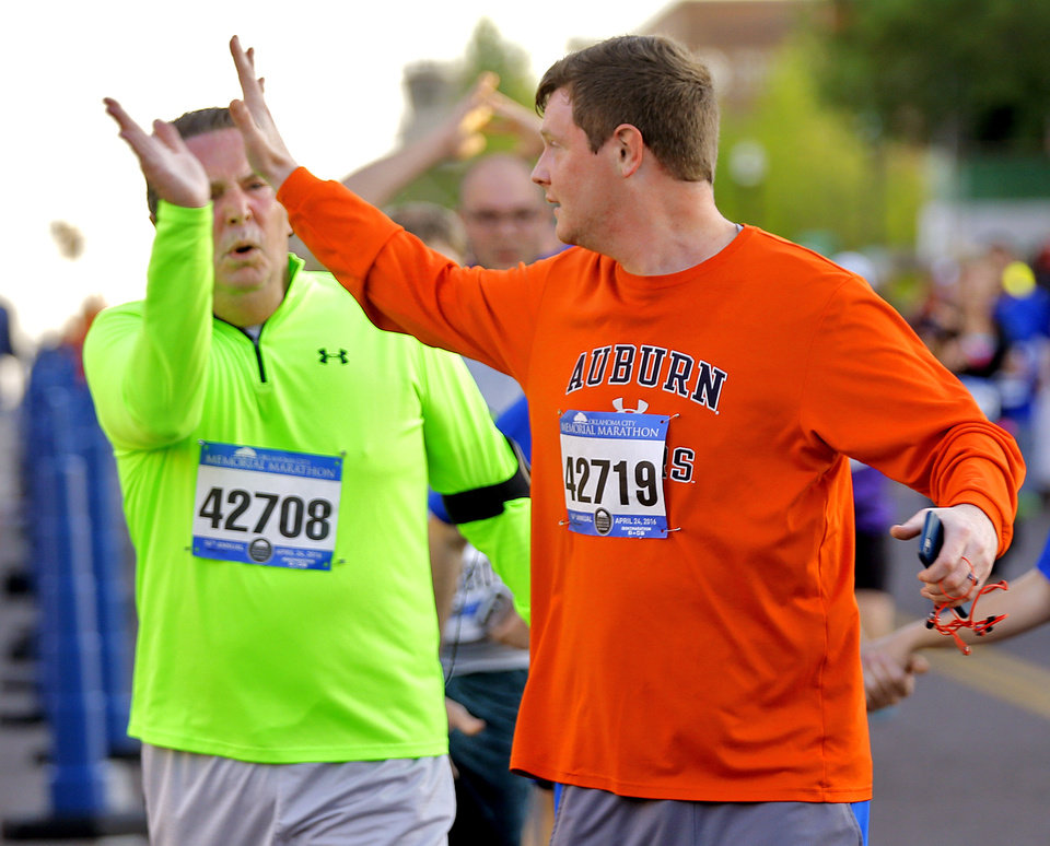 Photo - Steven and Patrick Nowlin, from left, high five after finishing the 5K during the Oklahoma Memorial Marathon in Oklahoma City, Okla. on Sunday, April 24, 2016.   Photo by Chris Landsberger, The Oklahoman
