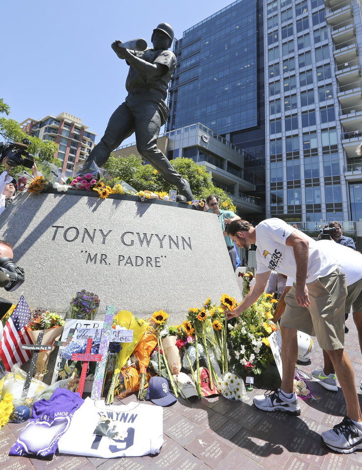 Photo - Members of the San Diego Chargers place flowers at the base of the Tony Gwynn