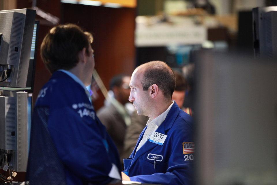 Photo -   FILE-In this Friday, June. 29, 2012, file photo, specialist James A. Denaro works the trading floor of the New York Stock Exchange before the closing bell. Stock futures are falling on the eve of the U.S. earnings season Monday, July 9, 2012,with more signs of instability coming out of Europe. (AP Photo/David Karp, file)